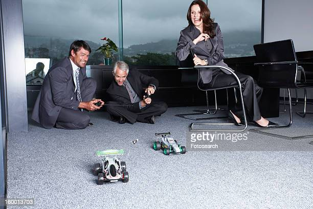 Businessmen playing with toys