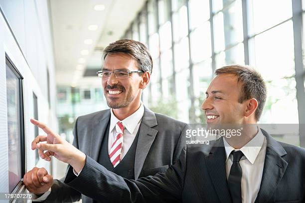 Businessmen pointing and looking at wall screen