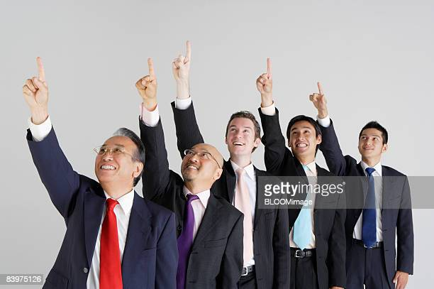 Businessmen pointing upward, smiling, studio shot