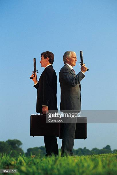Businessmen preparing to duel with pistols