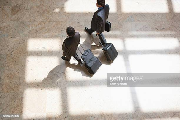 Businessmen pulling rolling suitcases