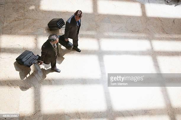 Businessmen pulling rolling suitcases