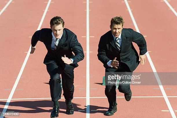 Businessmen racing each other on running track