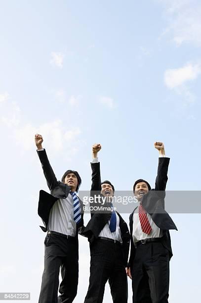 Businessmen raising fists against blue sky, portrait
