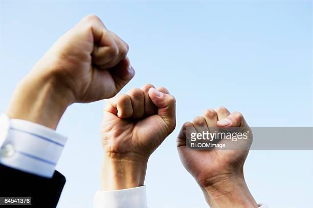Businessmen raising fists, focus on hands