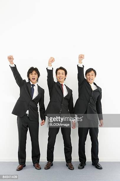 Businessmen raising fists, portrait