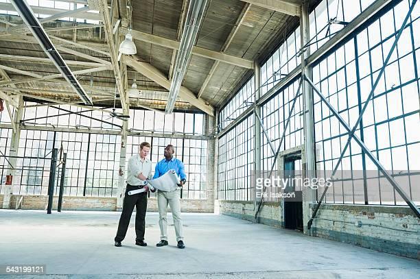 businessmen reading blueprints in empty warehouse - 商業不動産 ストックフォトと画像