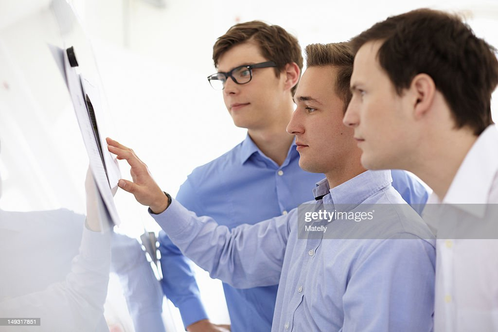 Businessmen reading together in office : Stock Photo