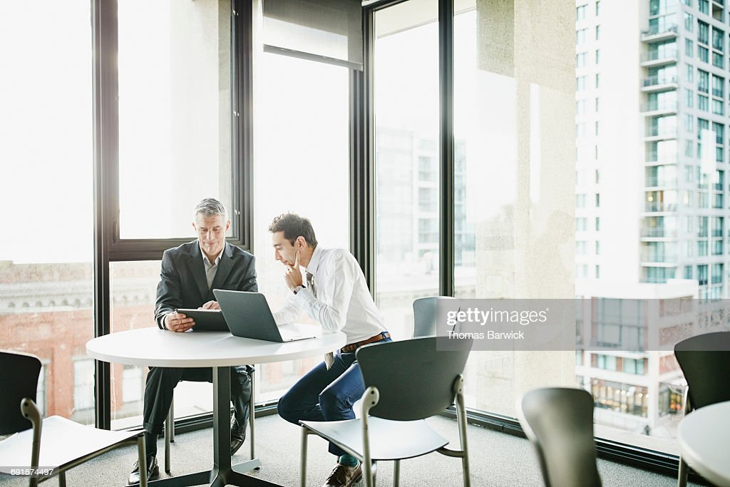 Businessmen reviewing data on digital tablet : Stock Photo