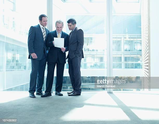 Geschäftsleute zum Überprüfen von Unterlagen nahe Glaswand im Büro