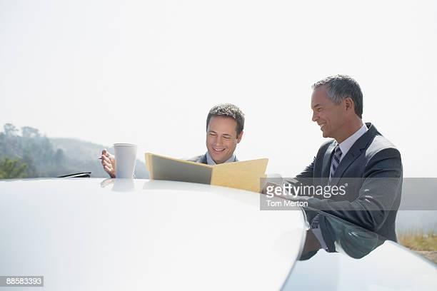 Businessmen reviewing paperwork outdoors