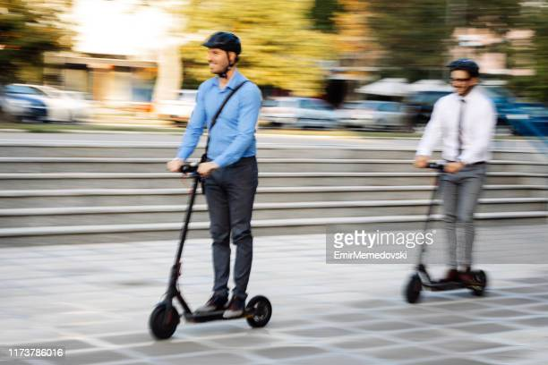 businessmen riding electric scooter - electric scooter stock pictures, royalty-free photos & images