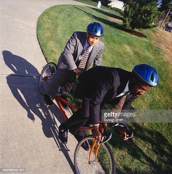 Businessmen riding tandem bicycle on path, elevated view