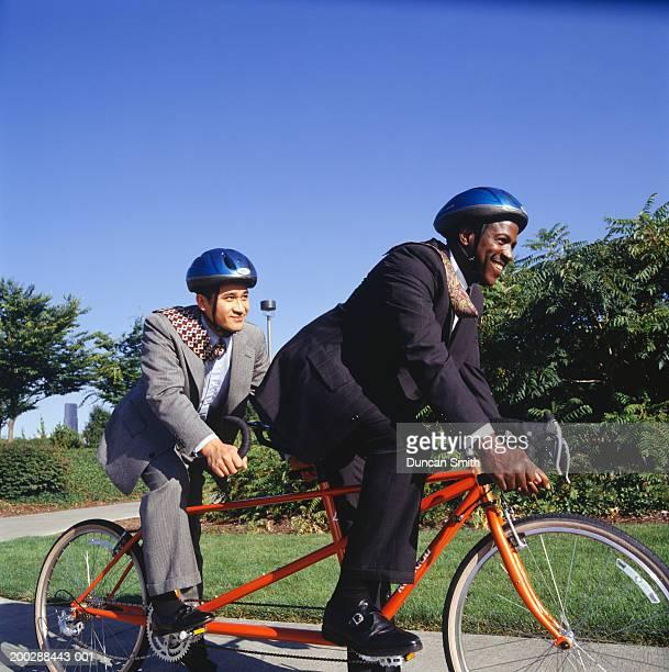 businessmen riding tandem bicycle - tandem bicycle stock pictures, royalty-free photos & images
