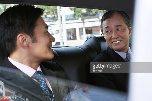 Businessmen riding together in taxi