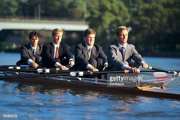 Businessmen rowing a scull