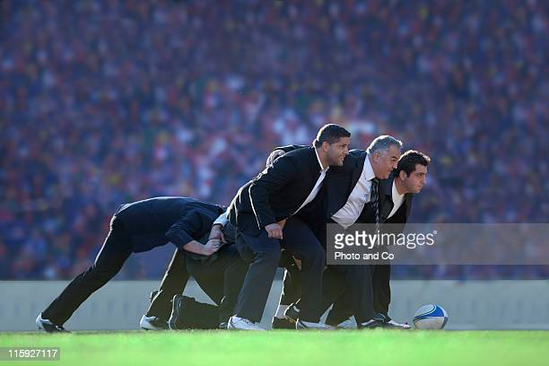 Businessmen rugby players in scrum on pictch