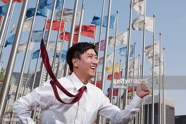 Businessmen running and smiling with flagpoles in background.