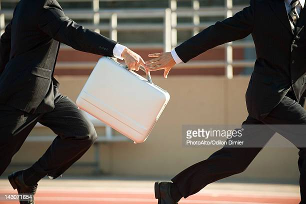 Businessmen running in relay race, handing off briefcase