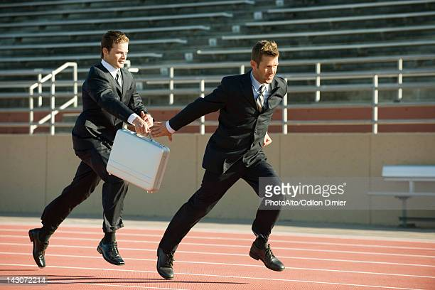 Businessmen running in relay race, handing off briefcase