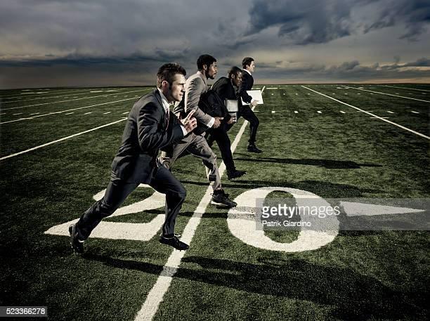Businessmen Running on Football Field