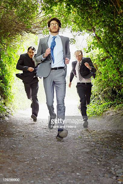 businessmen running on rural road - following stock pictures, royalty-free photos & images