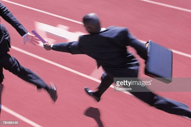 businessmen running on track and handing off baton - relay baton stock photos and pictures