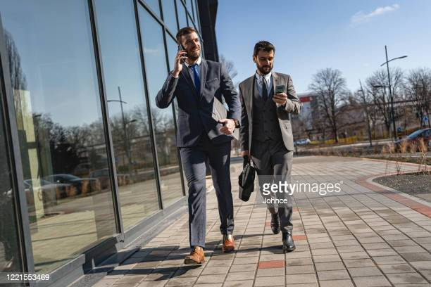 businessmen satisfied with news received via the phones - medium shot stock pictures, royalty-free photos & images