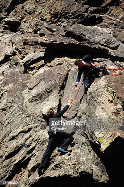 Businessmen scaling cliff