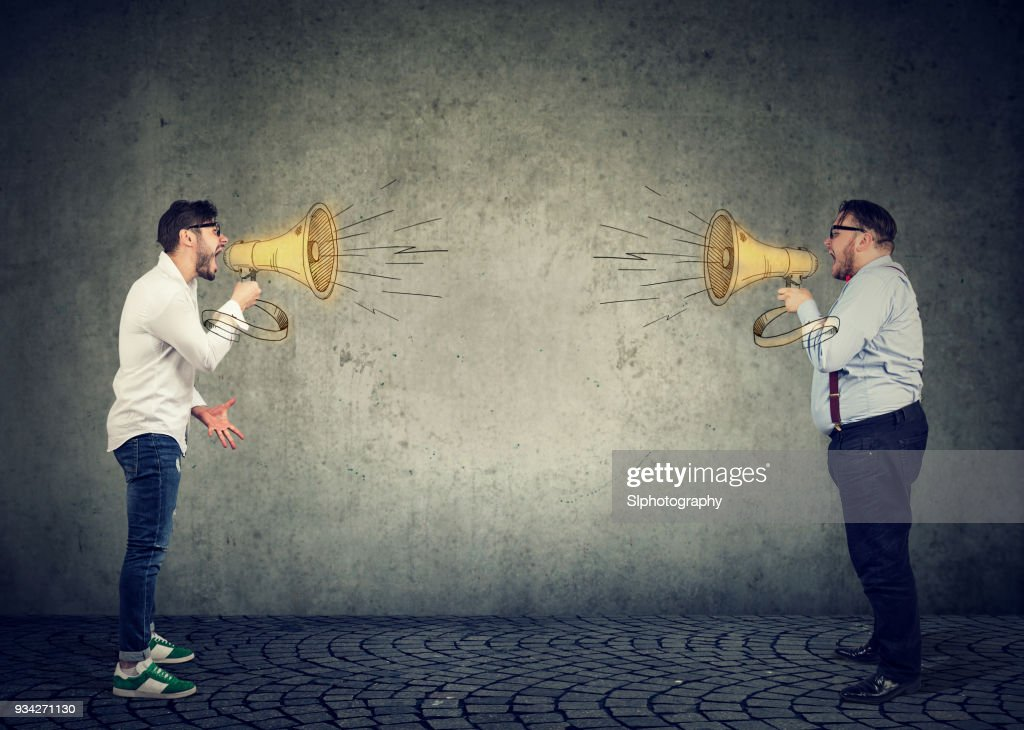 Businessmen screaming into a megaphone at each other : Stock Photo