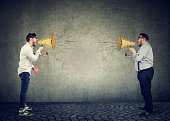 Businessmen screaming into a megaphone at each other