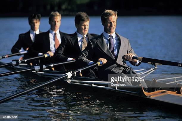 Businessmen sculling in rowboat