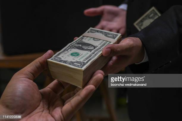 businessmen secretly passing money - bribery and corruption concepts - scammer stock pictures, royalty-free photos & images