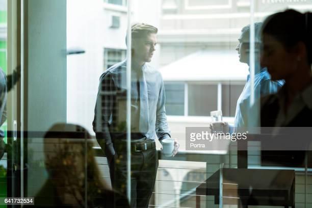 Geschäftsleute sehen durch das Glas während der Kaffeepause