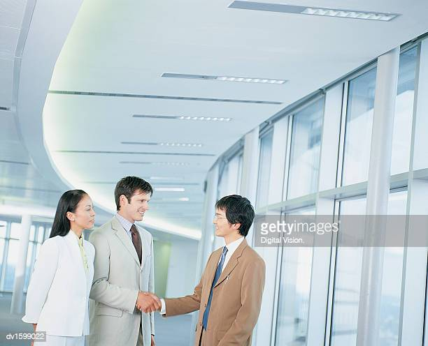 Businessmen Shake Hands as They Stand With a Businesswoman in an Office Corridor