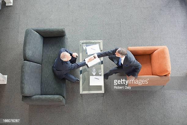 Hommes d'affaires se serrant la main sur la table à café dans le hall