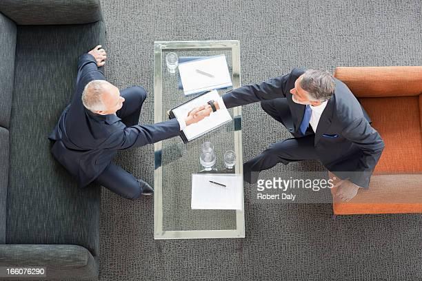 Geschäftsleute schütteln die Hände über Tisch in der lobby