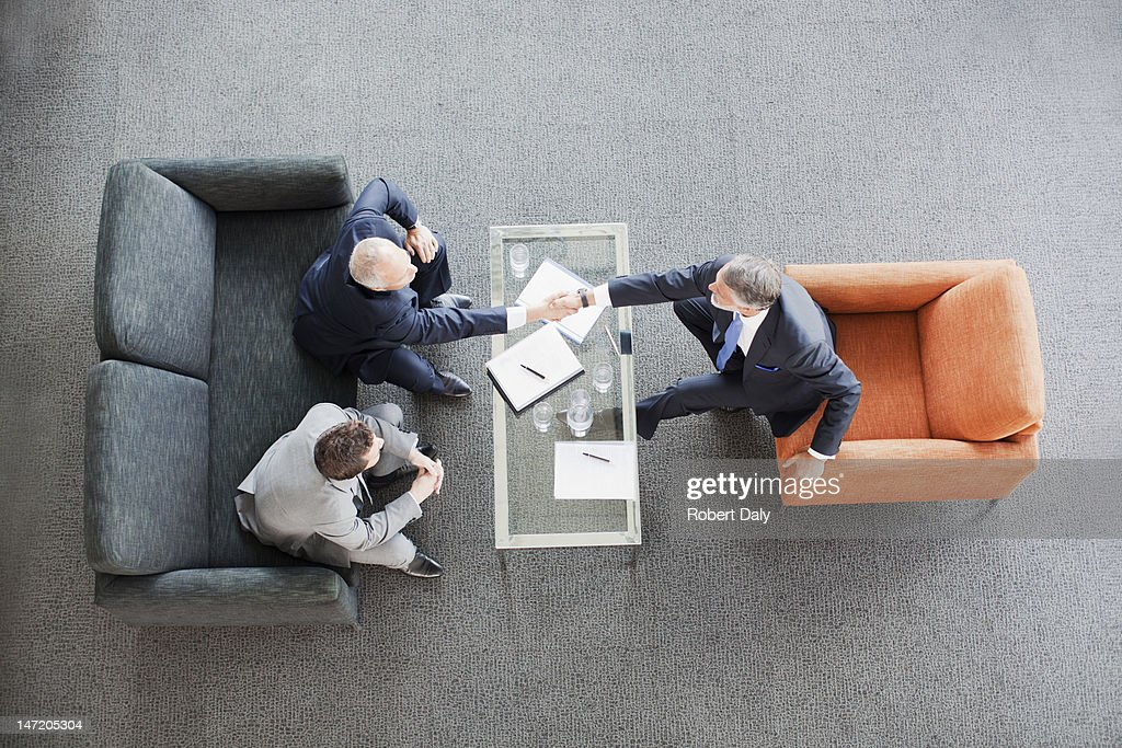 Businessmen shaking hands across coffee table in office lobby : Stock Photo
