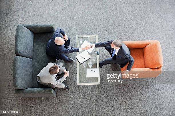 Businessmen shaking hands across coffee table in office lobby