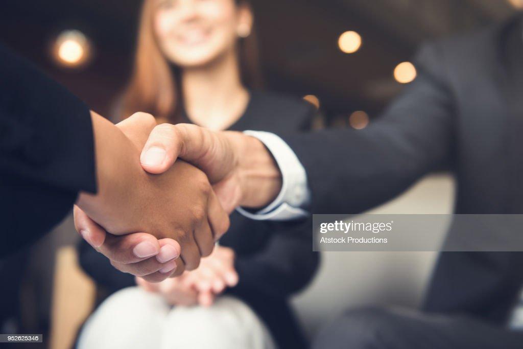 Empresários, apertando as mãos após a reunião em um café : Foto de stock