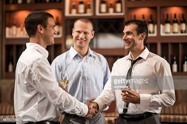 Geschäftsleute Händeschütteln und trinken Wein in einer bar.