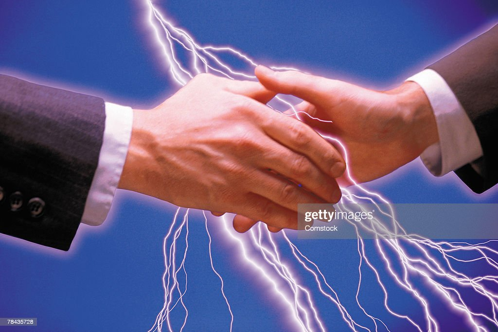 Businessmen shaking hands and lightning bolts : Stockfoto