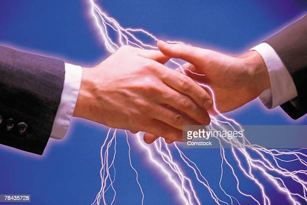 Businessmen shaking hands and lightning bolts