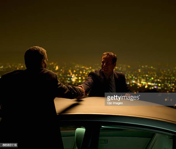Businessmen shaking hands at city overlook at night