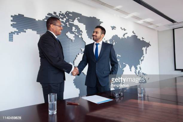 businessmen shaking hands at conference table - successor stock pictures, royalty-free photos & images