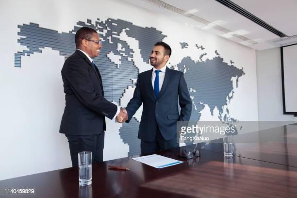 会議のテーブルで握手するビジネスマン - 後任 ストックフォトと画像