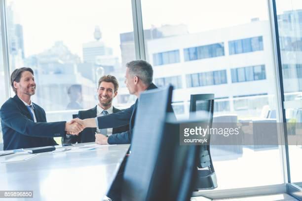 Empresarios estrecharme la mano en la mesa de la sala de junta.
