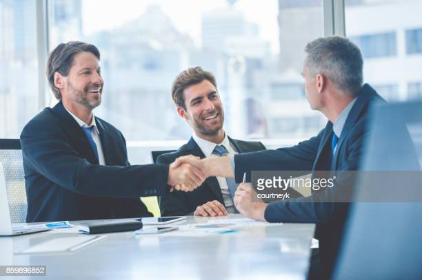 Businessmen shaking hands at the board room table.
