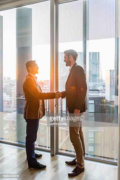 Businessmen shaking hands by modern office window