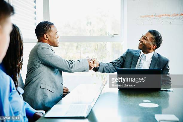 Businessmen shaking hands during meeting in office